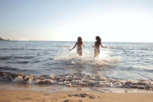 duas mulheres a correr para o mar