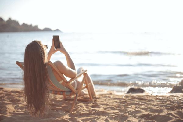 mulher a mexer no telemóvel sentada em cadeira na praia a apanhar sol