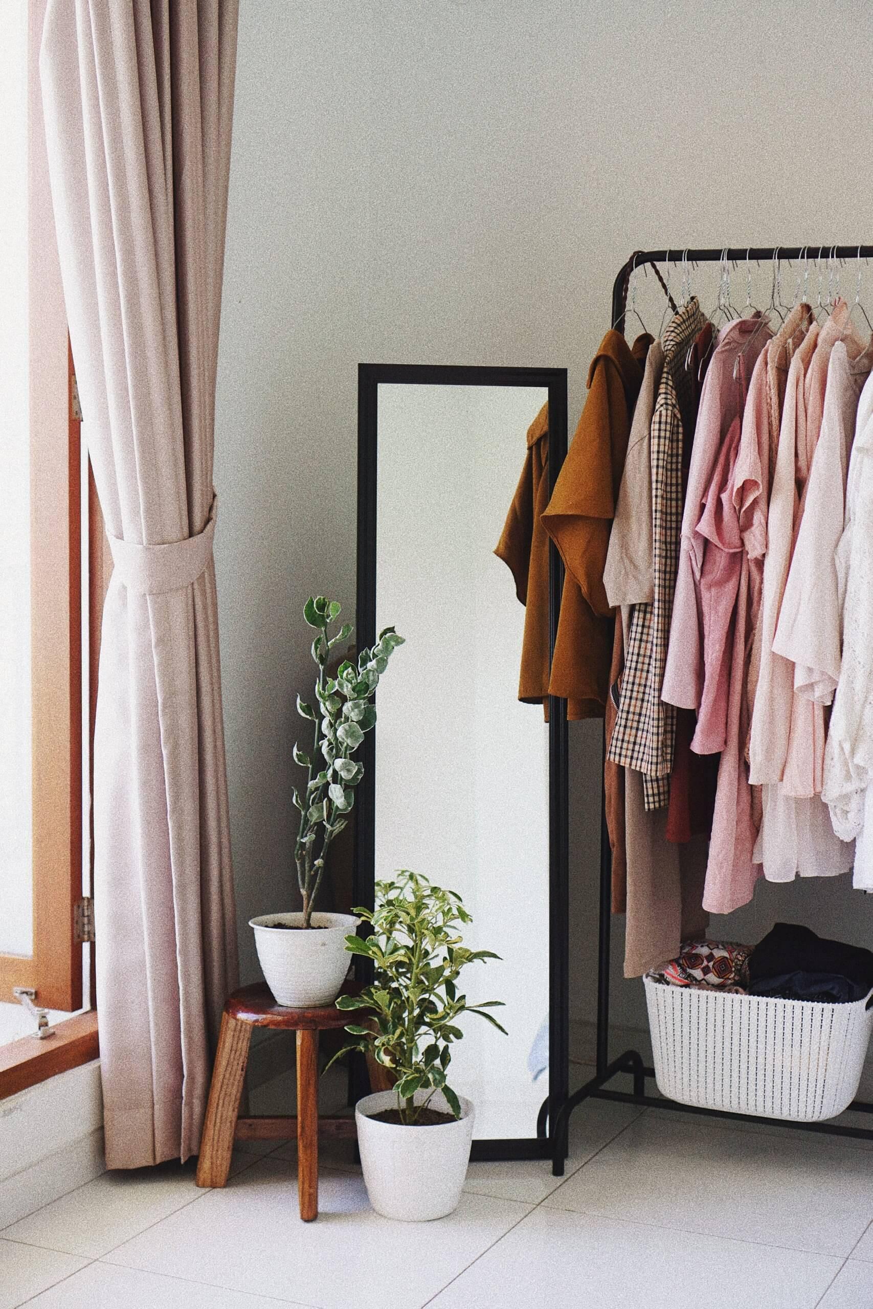 detalhe de quarto feminino com cabide com roupa em tons de cor-de-rosa, espelho, plantas e cortinado rosa