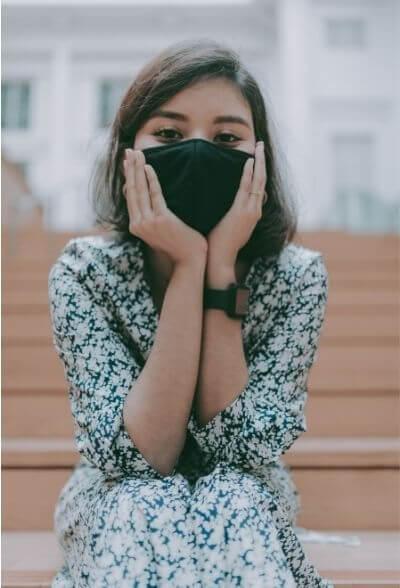 rapariga a usar máscara com a cara apoia nas mãos sentada numas escadas