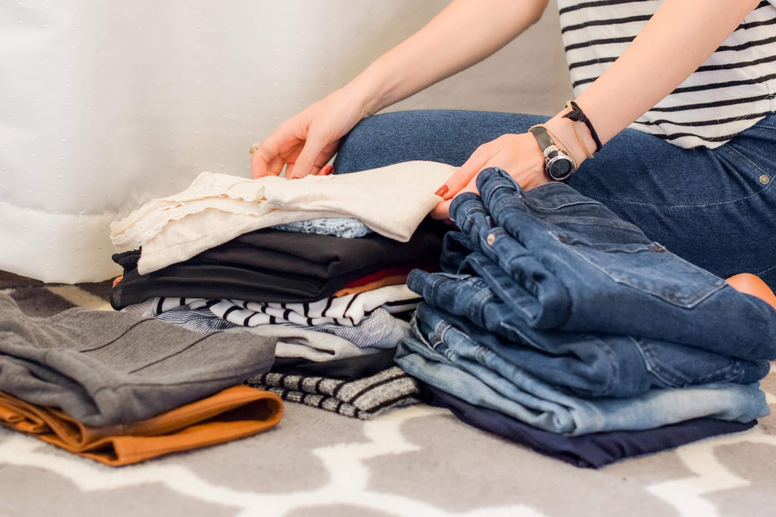 mulher a dobrar roupa em montes de roupa dobrada