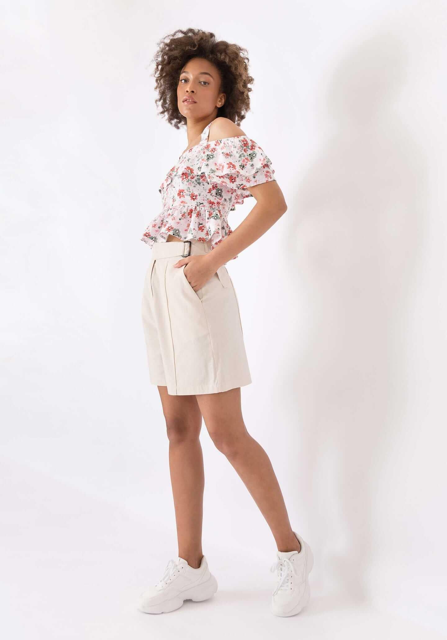 mulher molata de cabelo curto em sessão fotográfica a usar sapatilhas brancas, calções brancos e blusa branca com padrão de flores