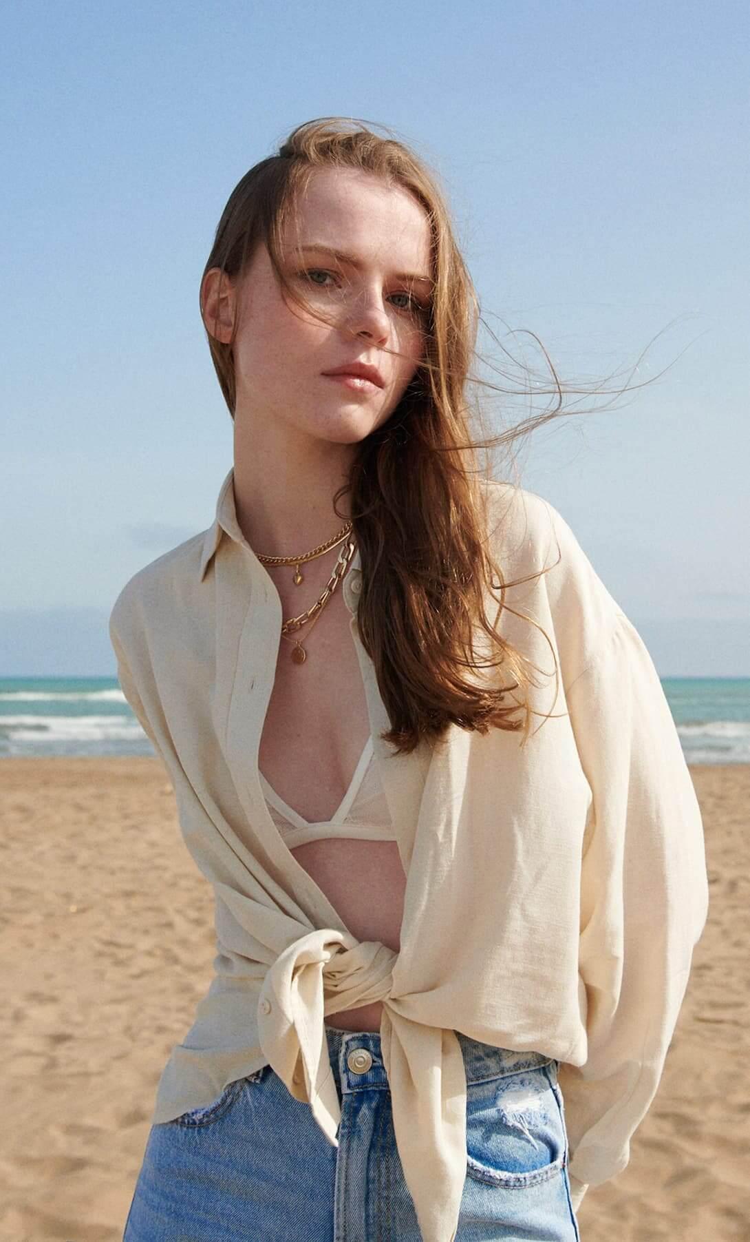 mulher de cabelo ruivo comprido em sessão fotográfica na praia a usar calças de ganga e camisa bege