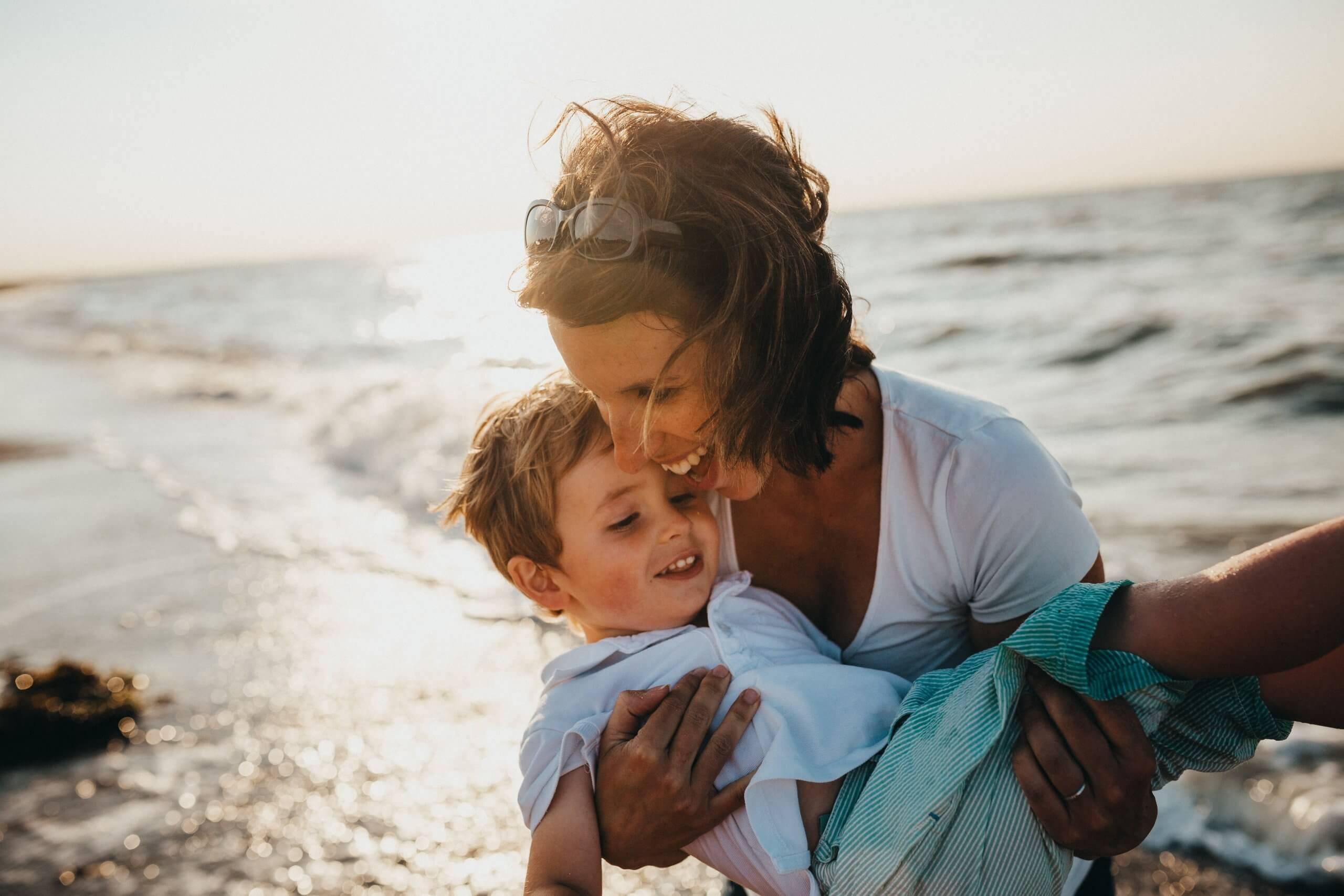 mãe e filho a a brincar na praia
