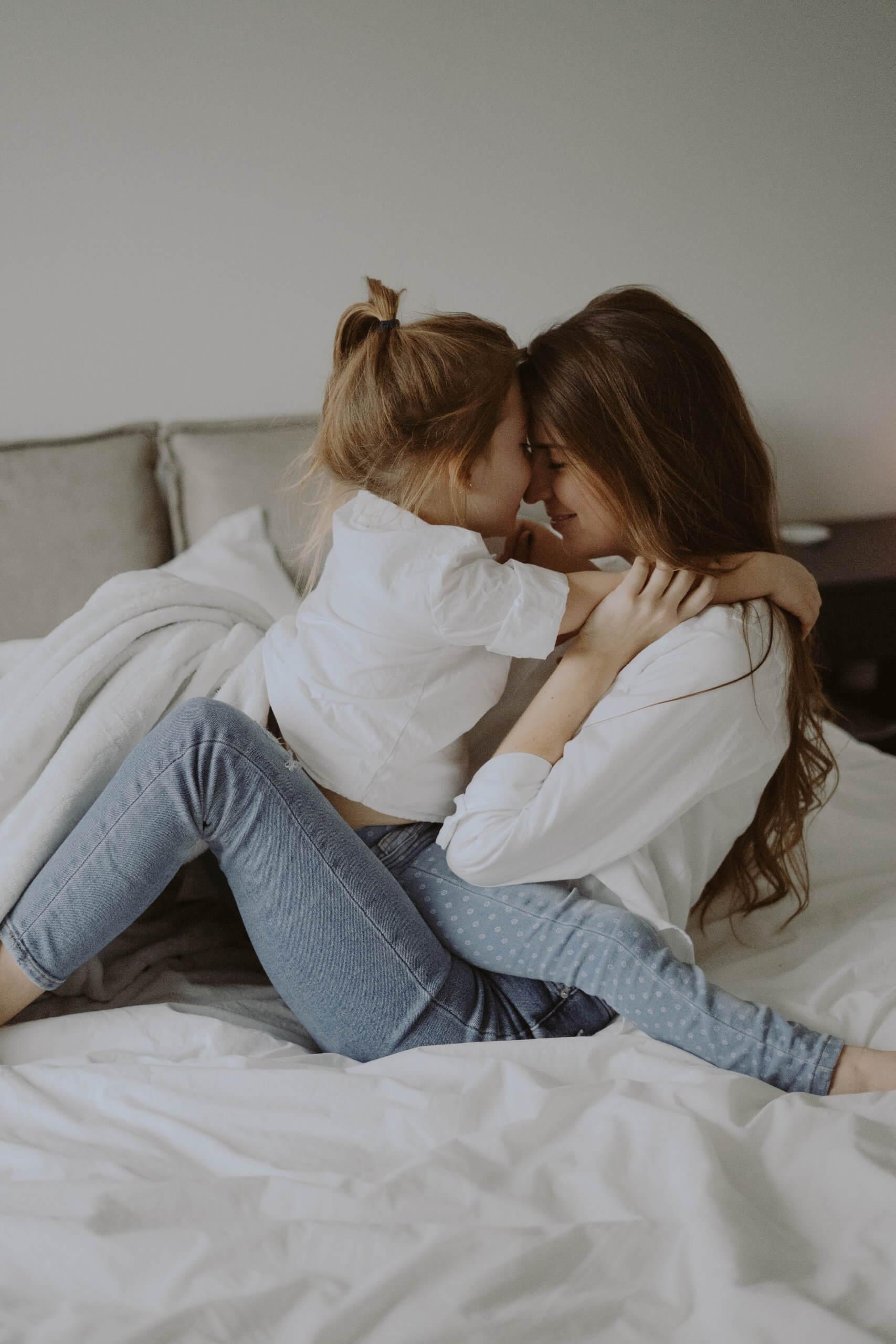 mãe e filha abraçadas na cama
