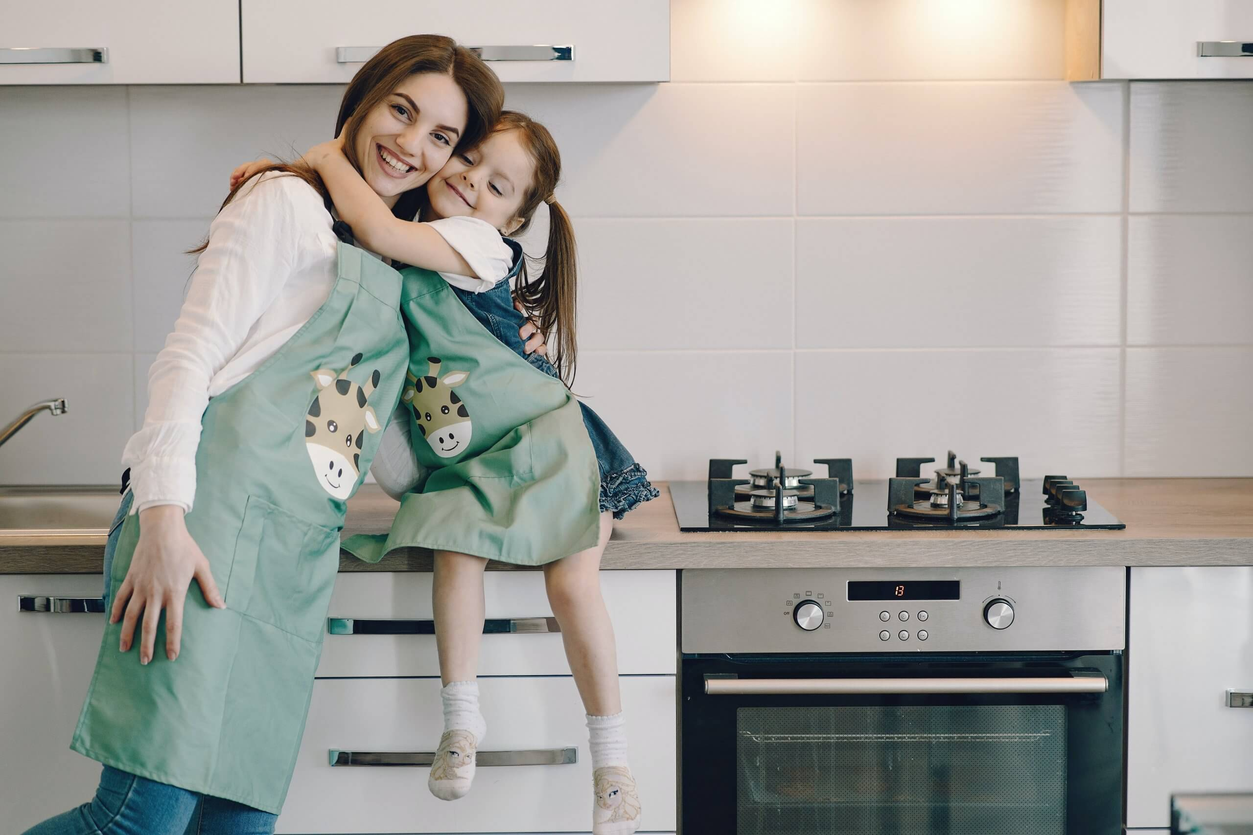 mãe e filha abraçadas na cozinha vestidas com aventais