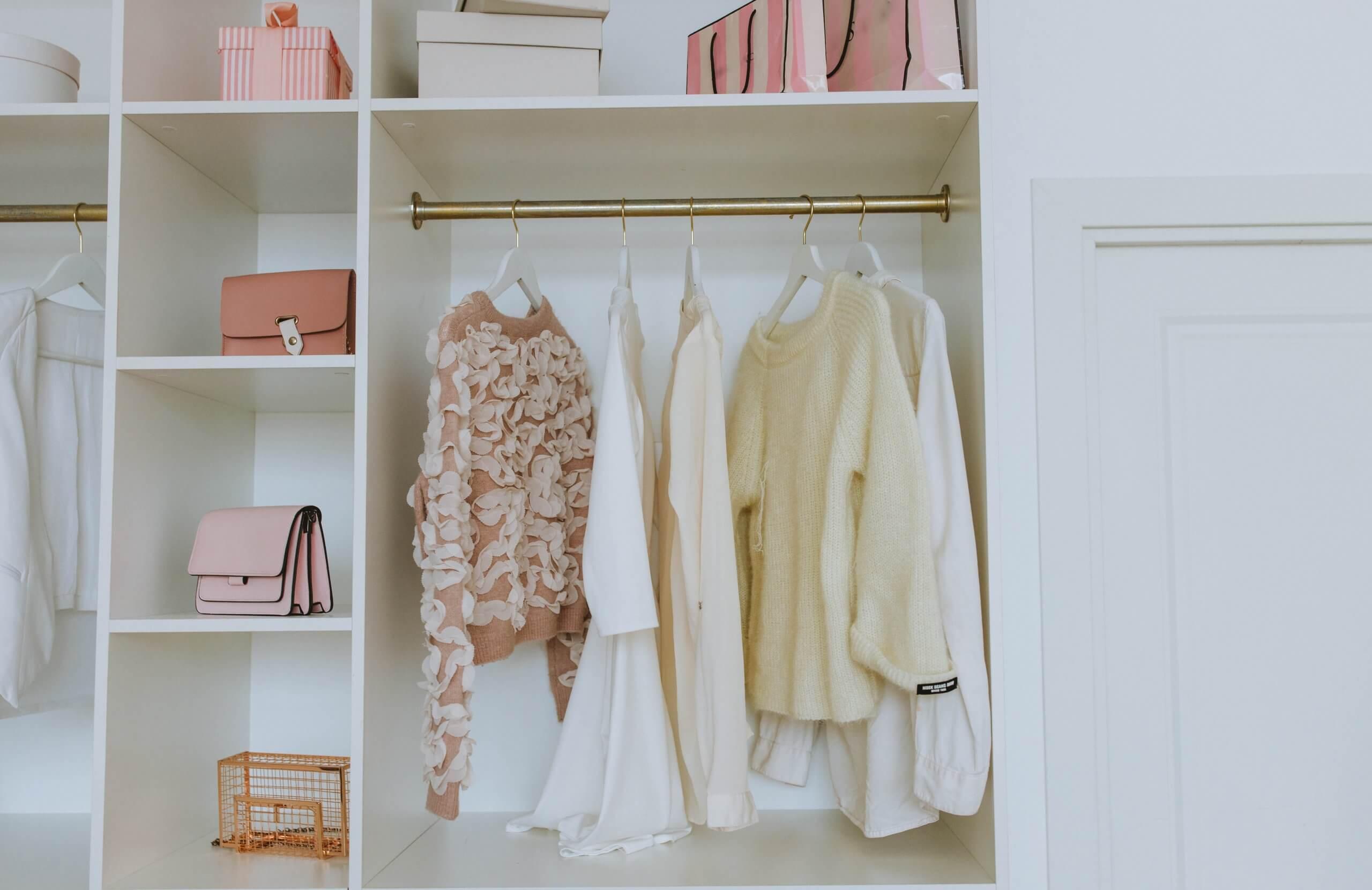 armário branco com roupa de mulher pendurada de cor de rosa e branco e malas em prateleiras