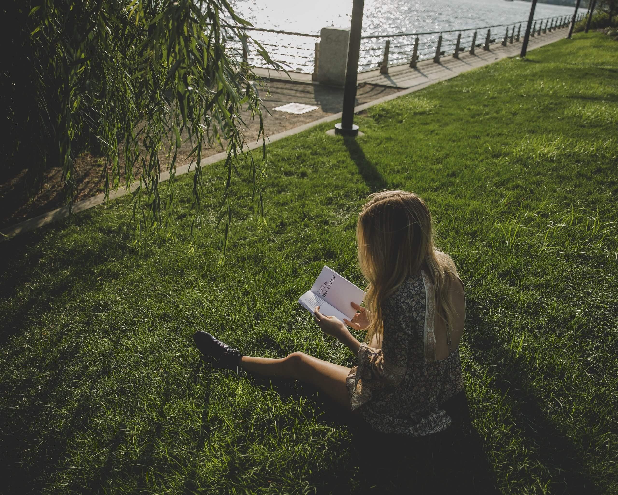 rapariga a ler um livro sentada num relvado junto à agua
