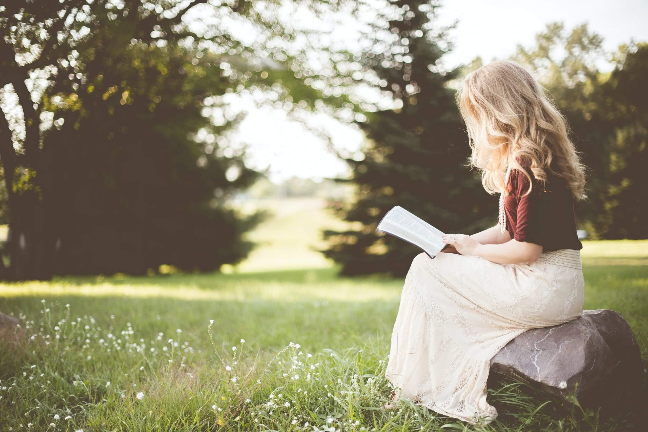 rapariga loira a ler um livro num parque sentada numa rocha